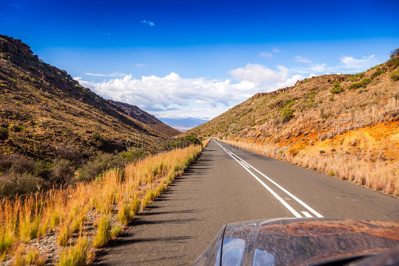 Road into adventure. Looking over a car bonnet at the tarmac road near Nieu Bethesda, leading into the mountains in the Karoo, South Africa. A great place for stock photos