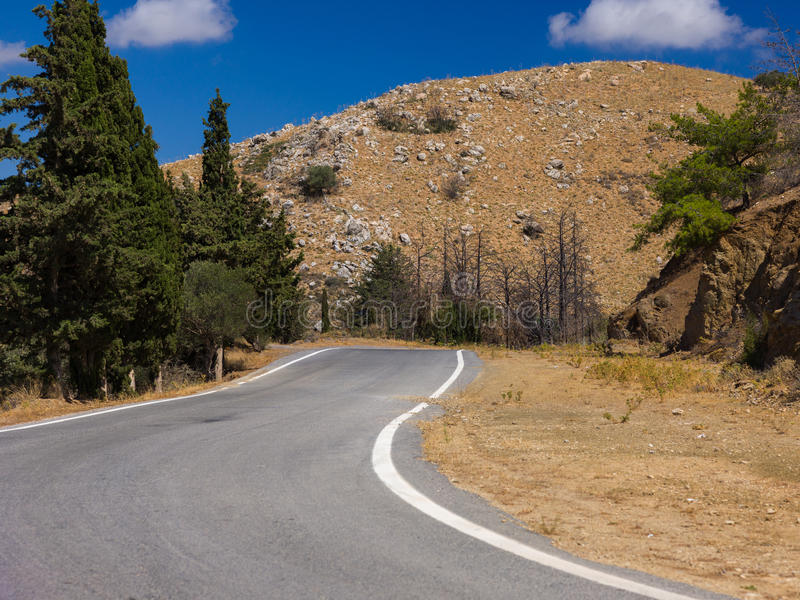 Road against mountains and pines and blue sky. royalty free stock photos