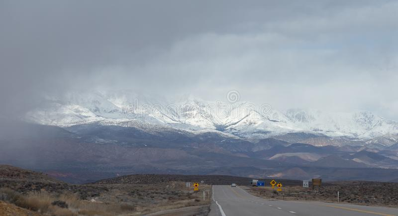 Road ahead into storm cloudy weather. And snowcapped mountain range in the background royalty free stock images