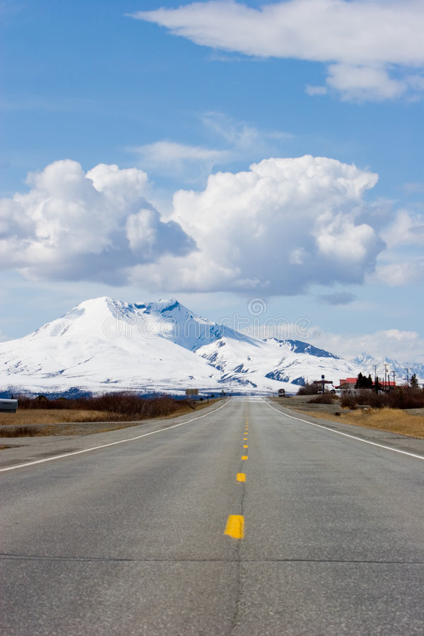 Road through Alaska mountains. Highway running by the snowy Alaska mountains royalty free stock image