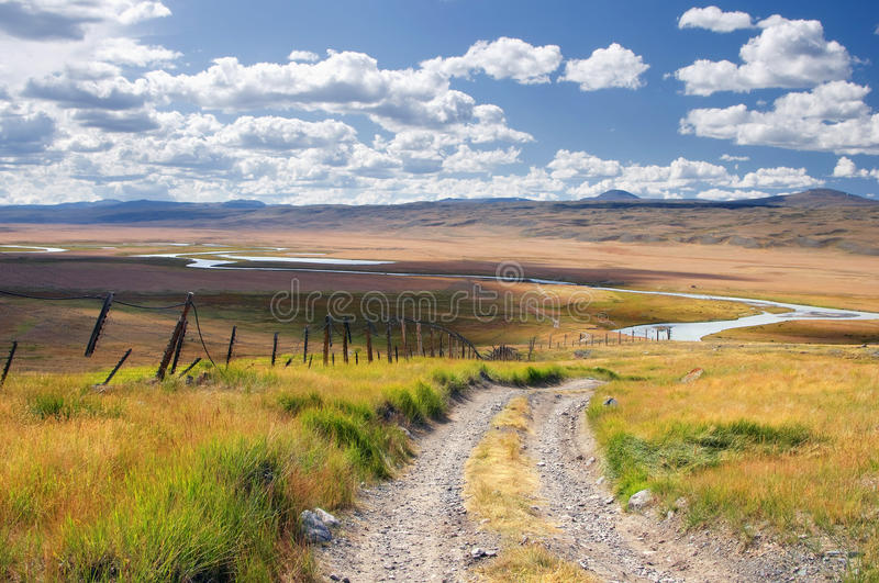 Road along the border line on a highland mountain plateau with the green grass at the background of the valley white river royalty free stock photos
