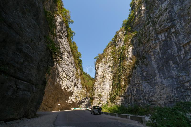 Road along the bottom of a deep canyon. An off-road car is parked at the side of the road stock images
