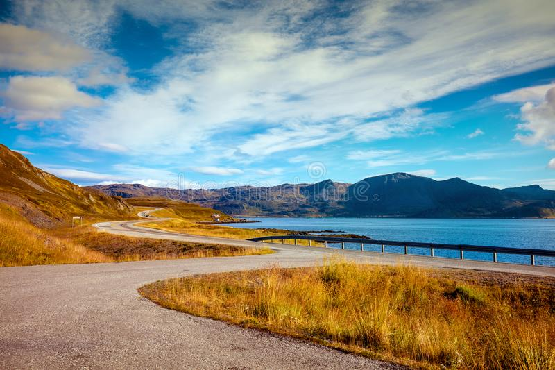 The road along the fjord on the island of Mageroya. Road to Nordkapp, Norway. Fjord with cloudy blye sky. Rocky shore. Beautiful nature Norway. Mageroya island royalty free stock images