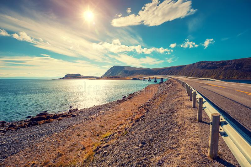 The road along the fjord on the island of Mageroya. Road to Nordkapp, Norway. Panoramic view at fjord with bridge. Beautiful nature Norway. Arctic bay. Mageroya royalty free stock images