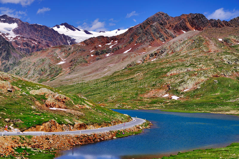 High Mountain Lake in the Dolomites, Italy. Road along the lake Lago Bianco near the top of the famous Gavia high mountain pass in Italy royalty free stock image