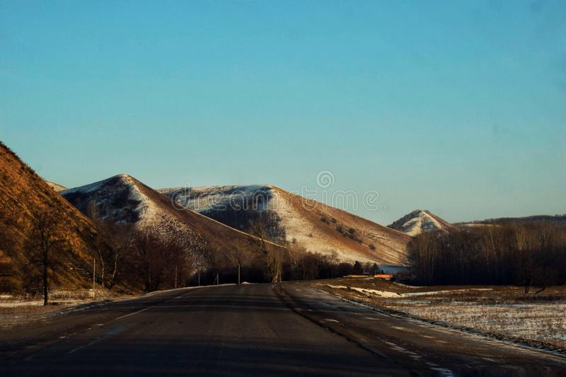 Snow-capped peaks of the Ural Mountains. The road along the snowy Ural Mountains stock image