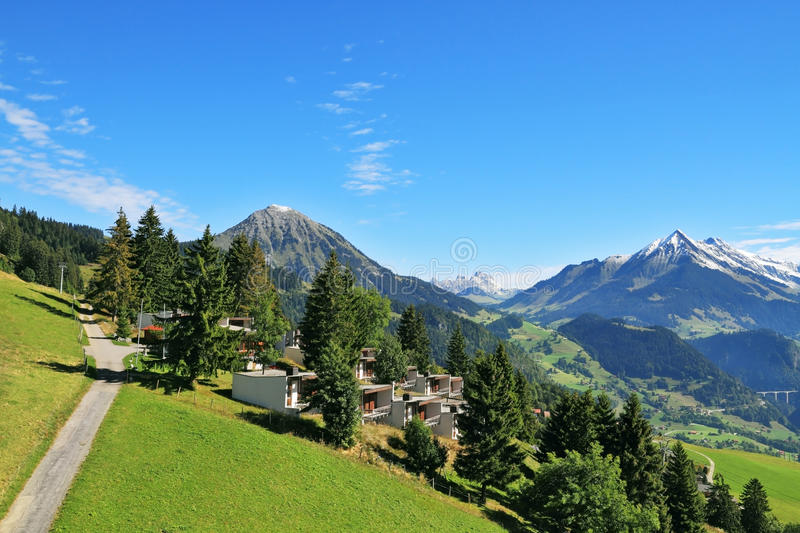 Road among alpine meadows and mountain chalet stock images