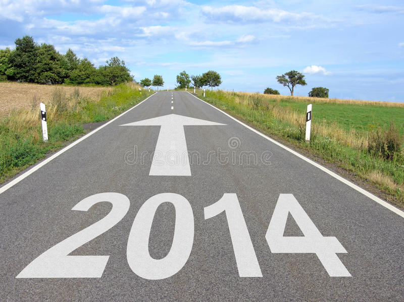 Road with arrow to year 2014. Road through agricultural landscape with white marking on tarmac of year 2014 and large arrow pointing to the horizon stock images