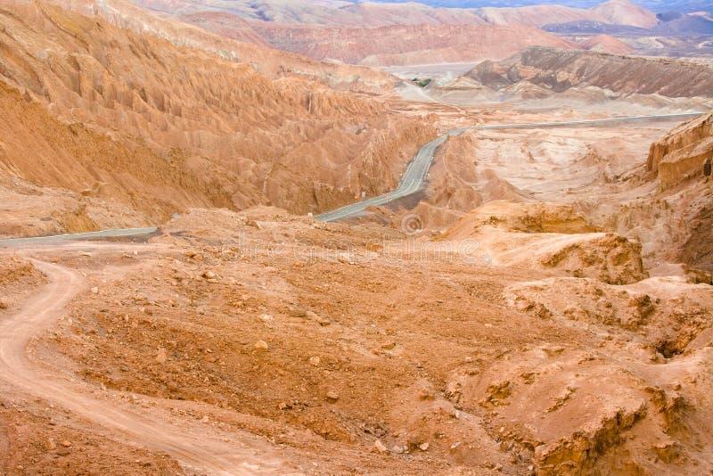 Road in the Atacama desert between salt formations at Valle de la Luna royalty free stock image