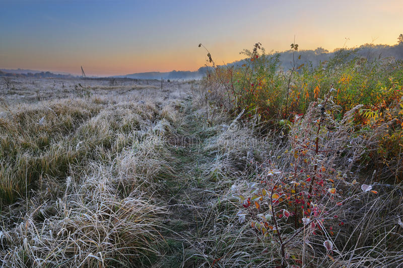 Road of autumn. Cold morning landscape with a river. Grass covered by hoarfrost stock photos