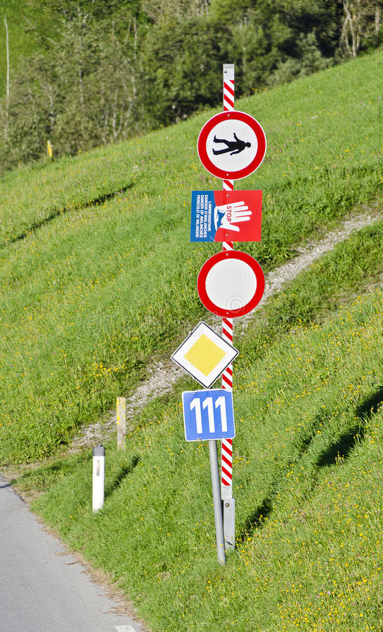 Road barrier and traffic signs. Barrier and road signs at an opened winter closure in summer stock images