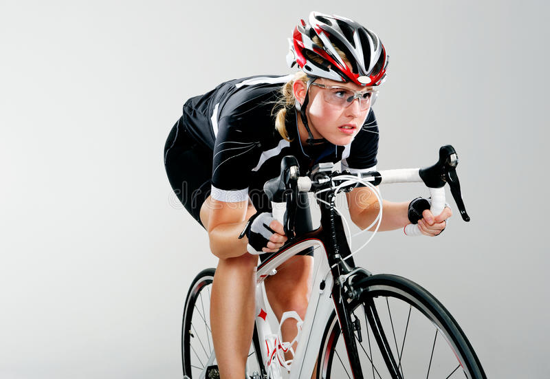 Road bike race cyclist. Road bicycle woman riding her bike in full cycle race gear royalty free stock photography