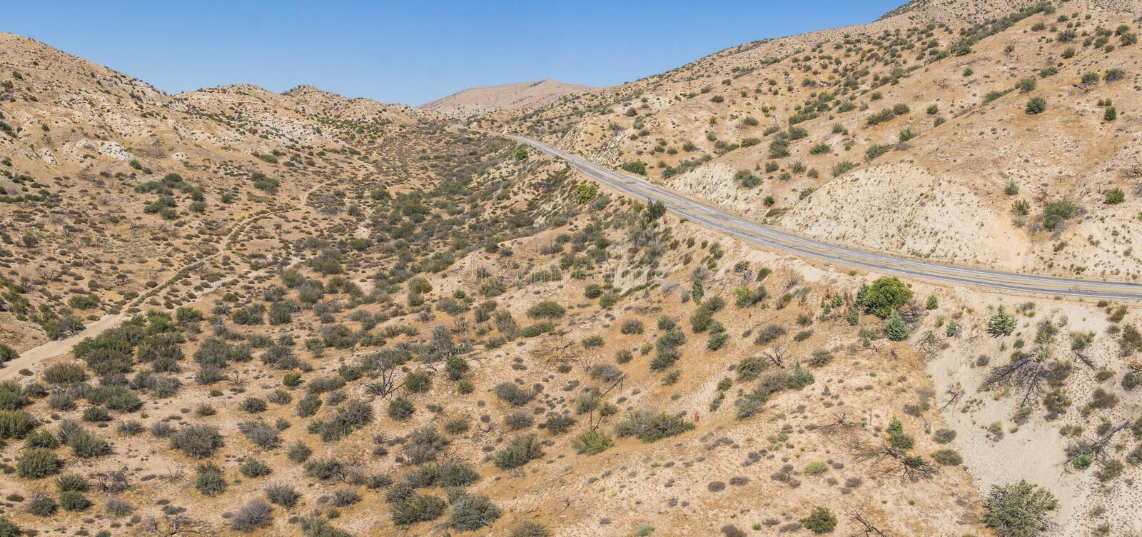 Road Bordering Mojave Desert Wilderness. Quiet empty road borders the vast wilderness of the Mojave desert in the southwest of United States stock photos