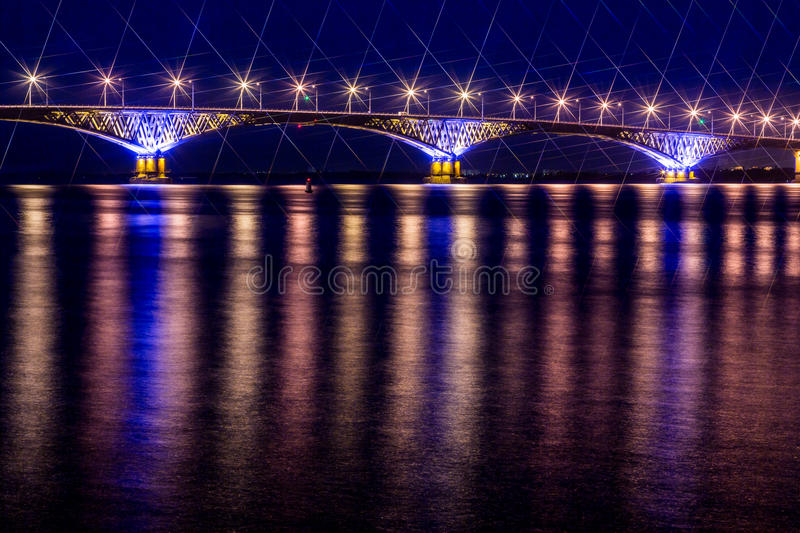 Road bridge across the Volga river between the cities of Saratov and Engels, Russia. Night or evening landscape. Golden street lights. The reflection in the stock photography