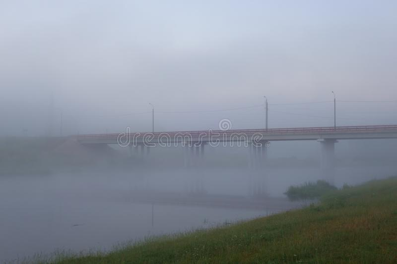 Road bridge over the river covered with predawn mist stock photo