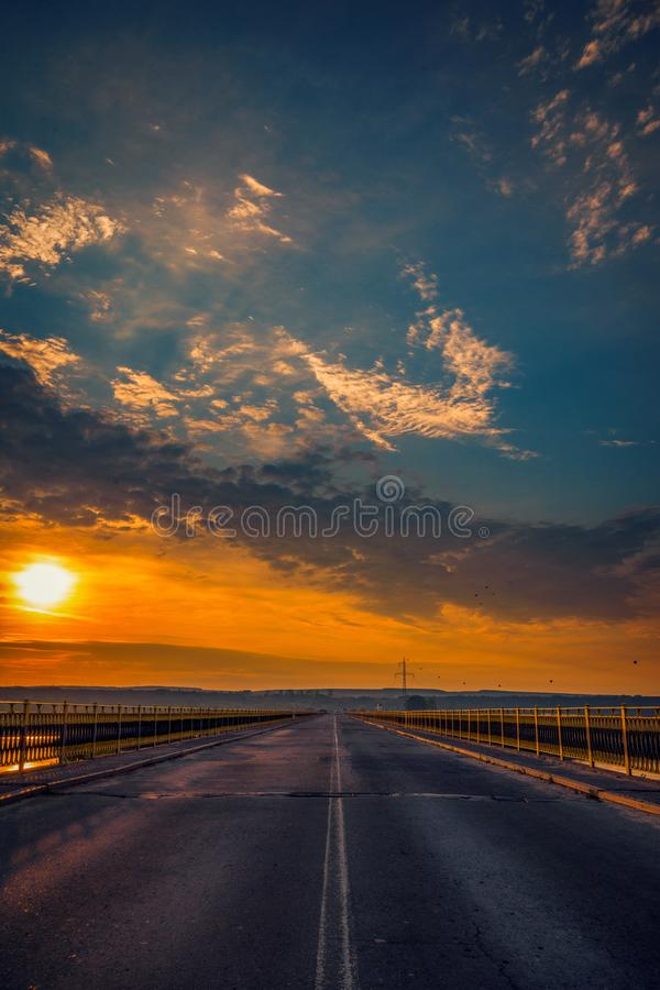 Road bridge over a river at sunrise against a blue sky with clouds stock photo