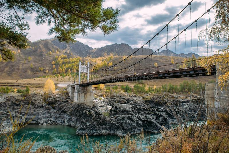 Road bridge over turquoise Katun river in Altai Mountains. Russian autumn in Siberia. Incredible landscape with a metal bridge royalty free stock image