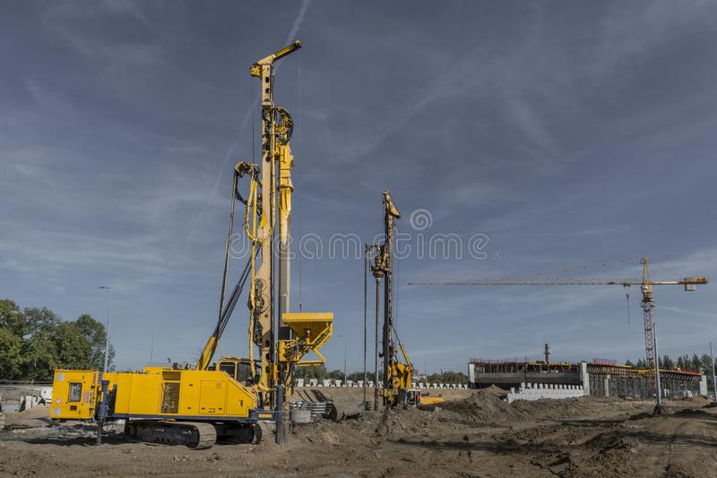 Road building with rotary drilling machine. Pile driving drilling machine working on road construction. Road building with drilling machine. Drilling machine royalty free stock image