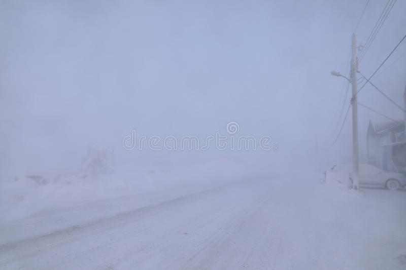 Road and buildings disappearing under blizzard conditions royalty free stock images