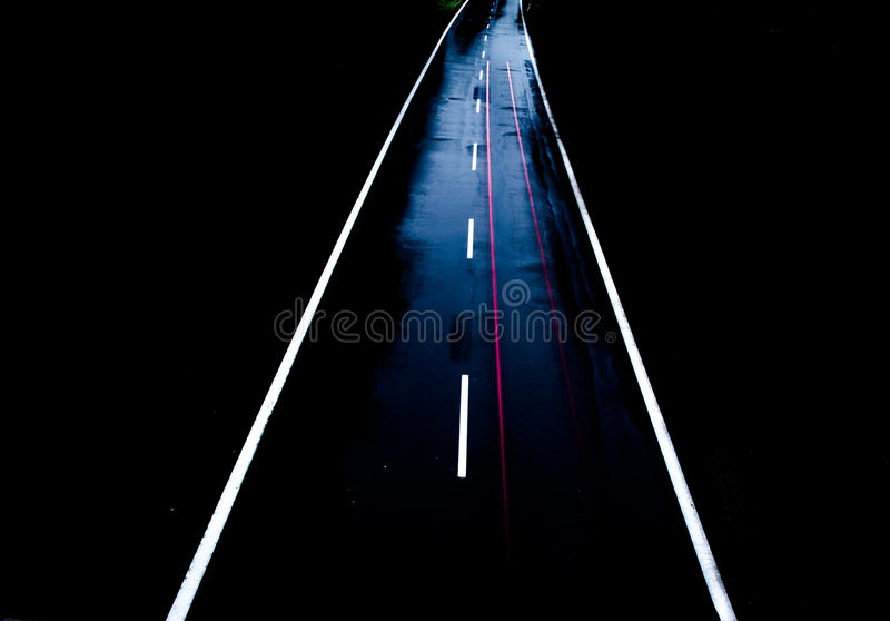 ROAD WITH CAR ALONE AT NIGHT WITH BLURRY LIGHTS royalty free stock photo