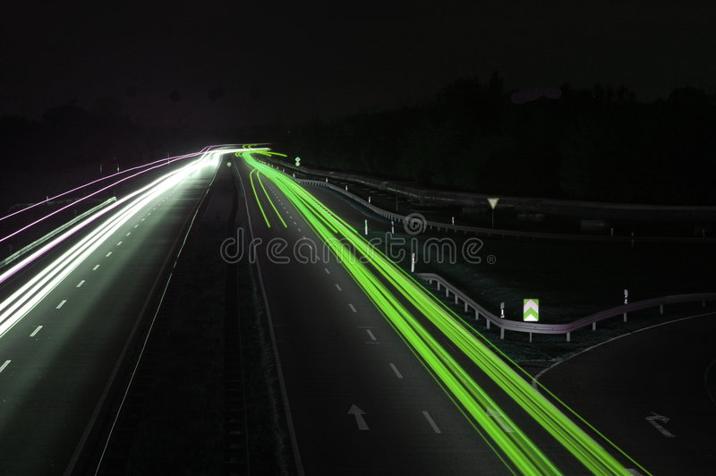 Road with car traffic at night with blurry lights stock photography