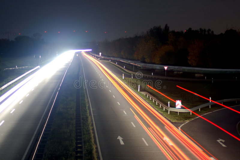 Road with car traffic at night with blurry lights stock image