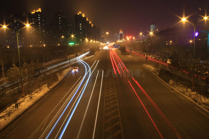 Road with car traffic at night with blurry lights stock photo