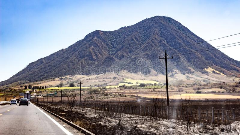 Road with cars circulating next to a meadow where there was fire with a mountain in the background. Arid field with electricity cables on a sunny day in the royalty free stock image