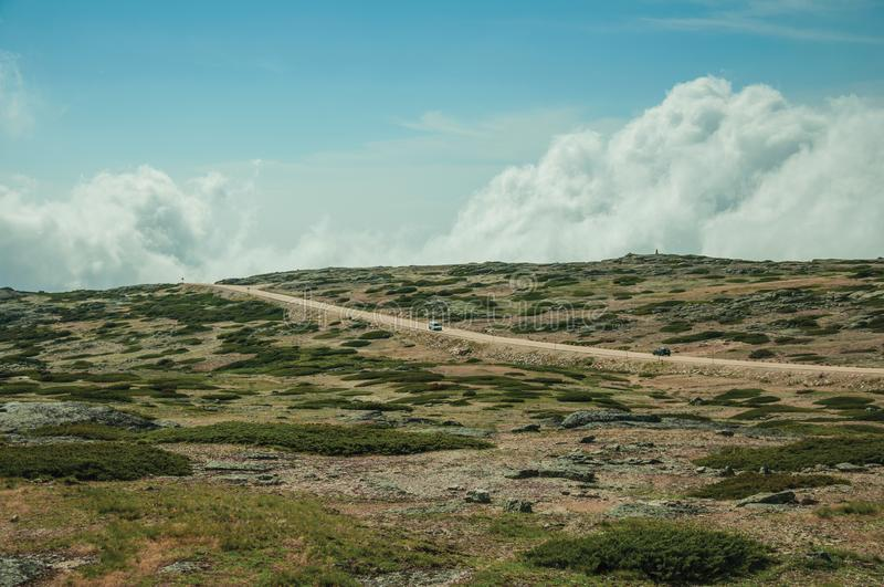 Road with cars passing through rocky landscape royalty free stock photo