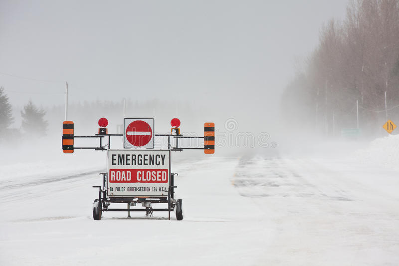 Road Closed. An emergency road closed barrier on the highway during a blizzard stock photography