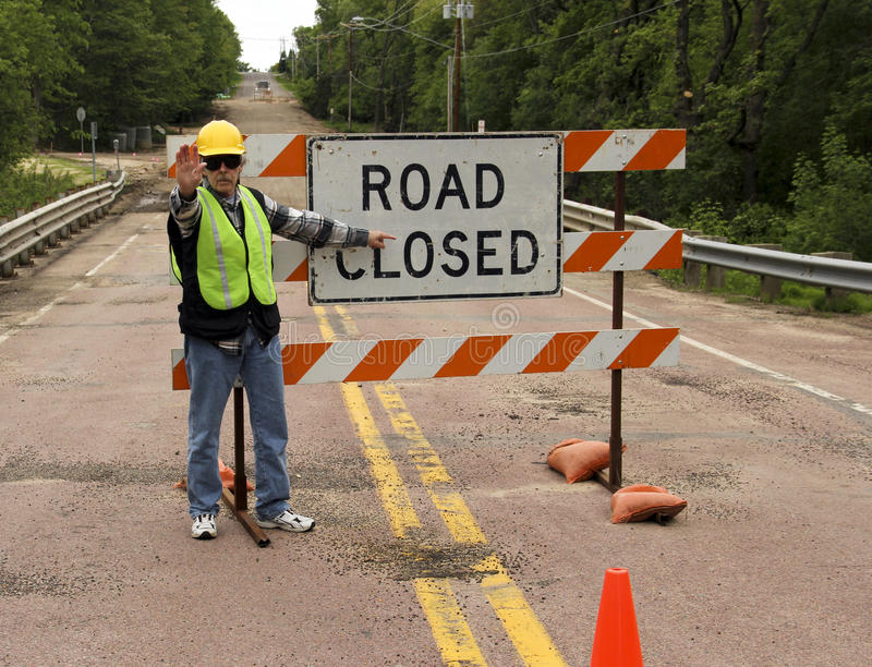 Road closed. Flag man points to a road closed sign on a highway royalty free stock image