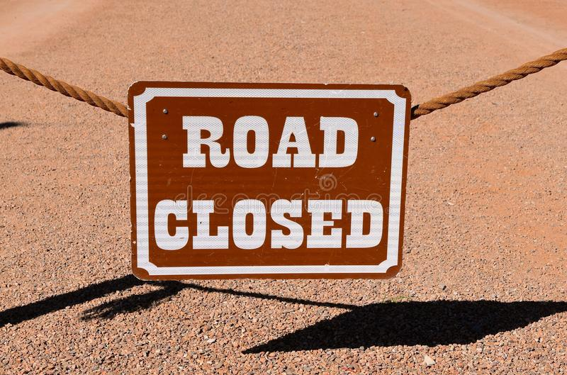 ROAD CLOSED sign hangs from a rope stock image