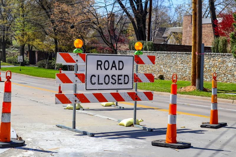 Road closed sign in the middle of four lane highway in residential neighborhood in early spring royalty free stock photography