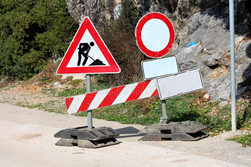 Road closed under construction metal road signs mounted on plastic holders on paved road with rocks and trees in back. Ground stock image