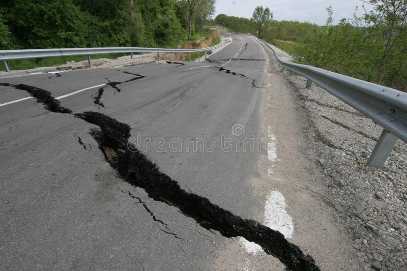 Road collapses with huge cracks. International road collapsed down after bad construction. Damaged Highway Road. Asphalt road. Road collapses with huge cracks royalty free stock photo