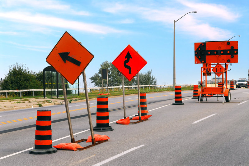 Road construction. Signs and cones on a city street stock photos