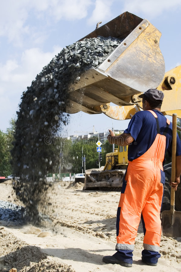 Road construction. Worker and road loader on the construction site stock image