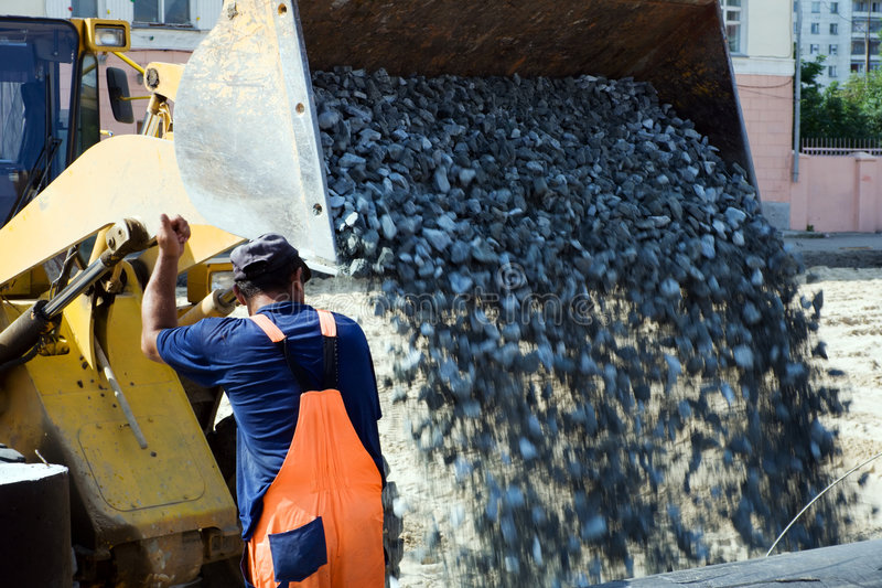 Road construction. Worker and road loader on the construction of road royalty free stock image