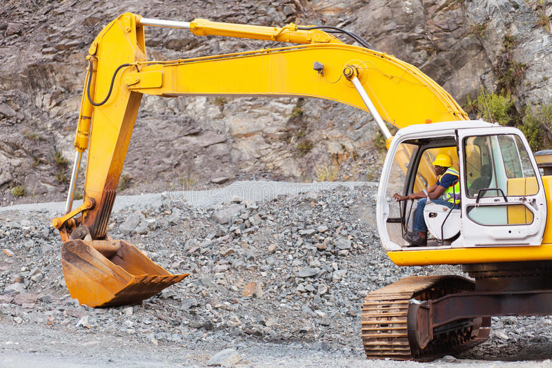 Road construction. African road construction worker operating excavator on construction site royalty free stock images