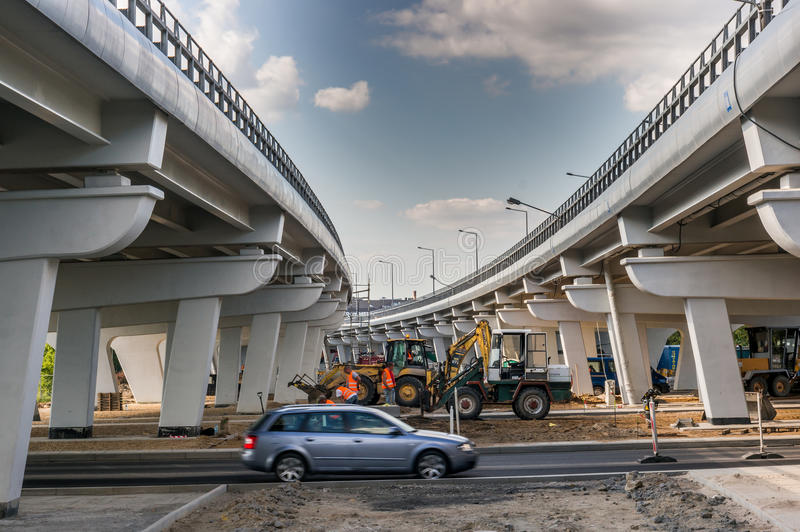Road construction by a bridge. Excavators doing road constructions by new build bridges with driving cars on August 2017 in Poznan, Poland stock image