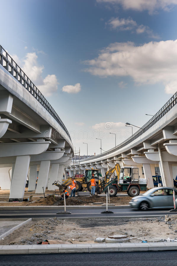 Road construction by a bridge. Excavators doing road constructions by new build bridges with driving cars on August 2017 in Poznan, Poland royalty free stock image