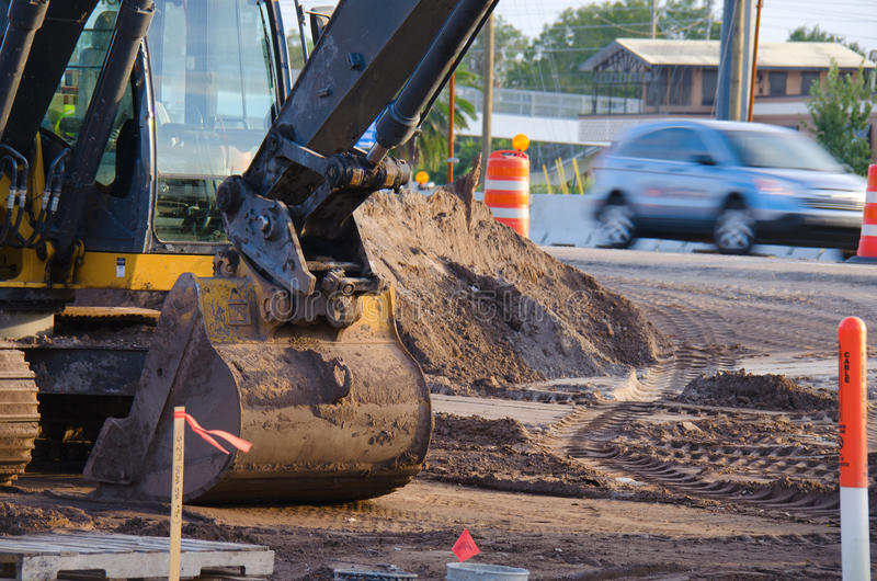 Road construction. With a bulldozer, road hazard barricades and piles of dirt with a car driving by stock photo
