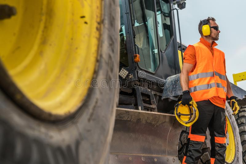 Road Construction Business. Caucasian Heavy Machinery Operator in His 30s with Noise Reduction Headphones and Hat Protection Helmet in a Hand royalty free stock photos