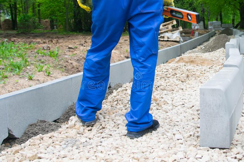 Road construction and installation of curbs in the Park, the feet of the worker in blue uniform royalty free stock photos