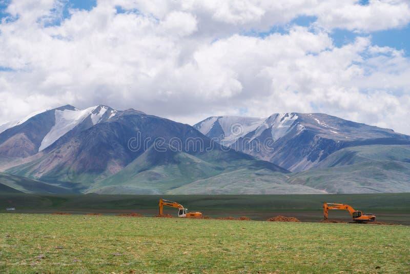 Road construction in Mongolia. Excavators perform earthworks. KHOVD, MONGOLIA - JULY 06, 2017: Road construction in Mongolia. Excavators perform earthworks royalty free stock photos