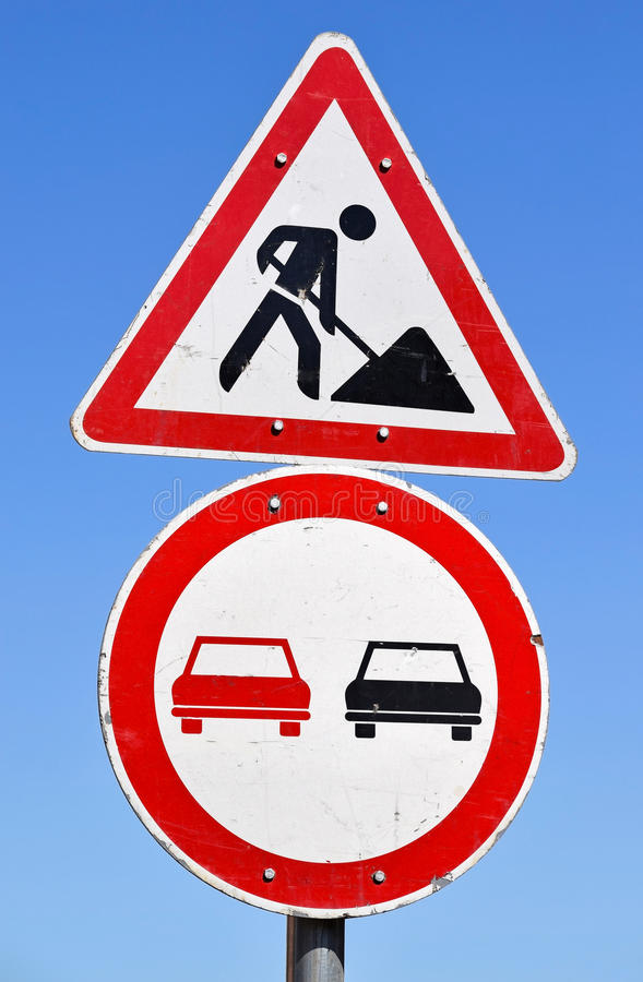 Road construction and no overtaking traffic signs. On the street stock images