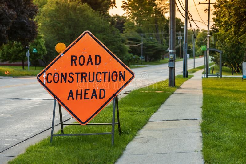 Road construction sign by the road sign. A road construction sign by the road sign royalty free stock photography