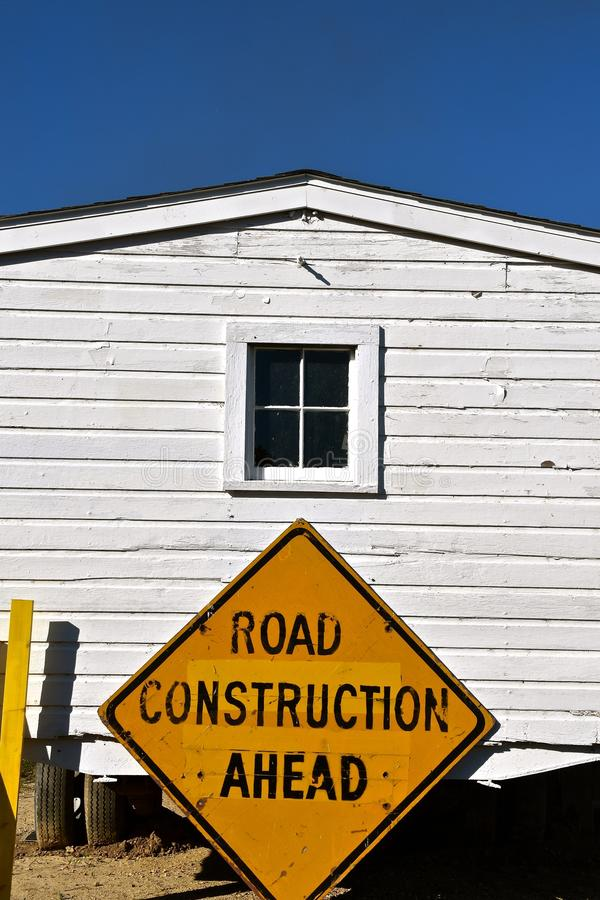 `Road Construction Sign`. A warning sign `Road Construction Ahead` where an old building is being moved stock image