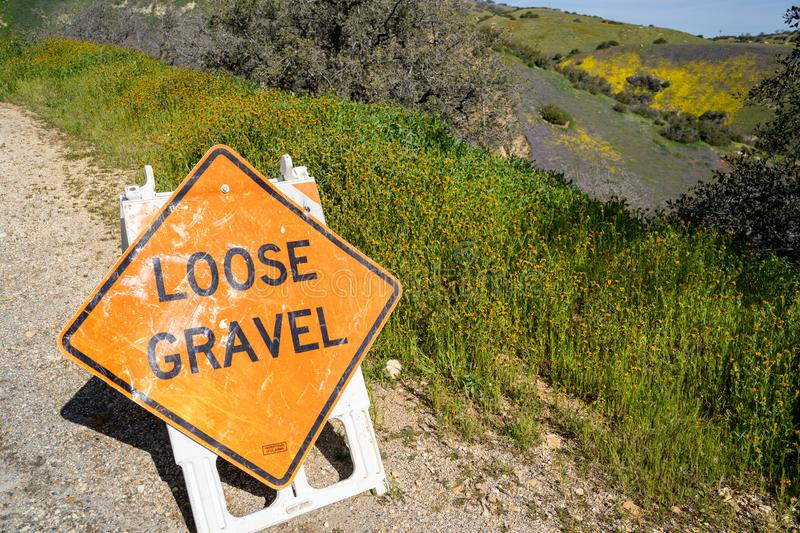 Road construction sign warns drivers of loose gravel ahead stock images