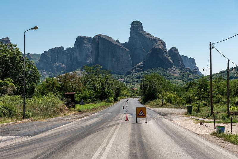 Road Construction Sign on the way to the mountains. Rock formations near Meteors or Meteora, Thessaly, Greece stock images
